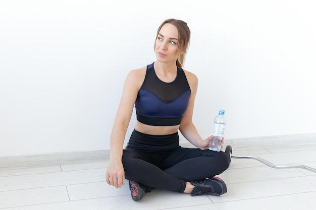 人々、スポーツ、フィットネスのコンセプト-ジムのマットの上に水のボトルと一緒に座っている若い女性。