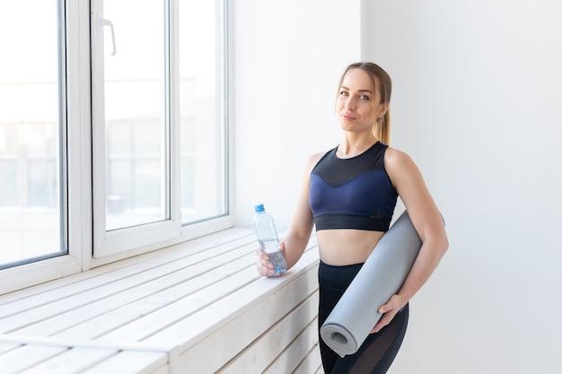 人々、スポーツ、フィットネスのコンセプト-窓の近くに立っているヨガマットと水のボトルを持つ若い女性。
