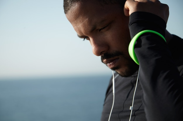 People and sport concept. good-looking young athlete in black outfit listening to his favourite tracks in headphones using mobile phone, touching his head, thinking about his goals and achievements