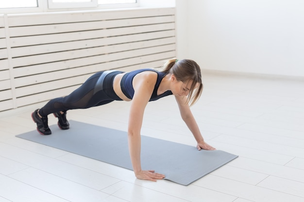 People, sport and fitness concept - young beautiful sportswoman doing push ups