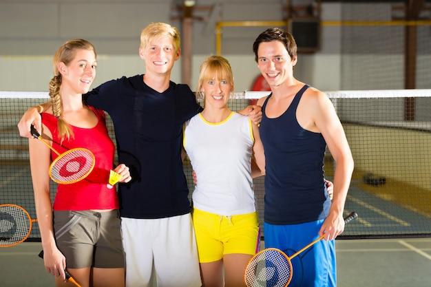 People in sport gym before badminton