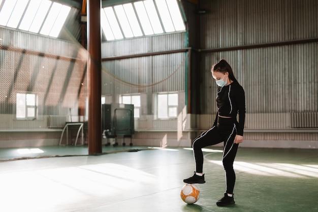 사람들 스포츠 레저 개념 젊은 여성 축구 팬 코로나바이러스 지원 좋아하는 팀에서 안전을 위해 얼굴 마스크를 쓰고 빈 코트에서 공을 멈추고 팬 지지자가 없습니다.