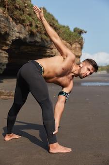 Persone e concetto di motivazione sportiva. l'uomo atletico fa esercizi, utilizza l'app in esecuzione sullo smartphone