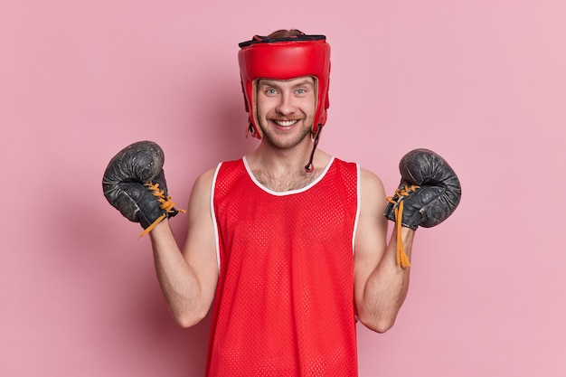 People sport motivation concept. positive man has training in gym wears protective headgear boxing gloves t shirt has cheerful expression after winning sport game