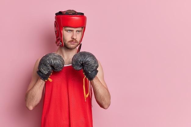 사람들이 스포츠 동기 부여 개념. 진지한 남성 복서는 보호용 모자 셔츠와 권투 글러브를 착용하고 펀치가 챔피언이되기를 원합니다.