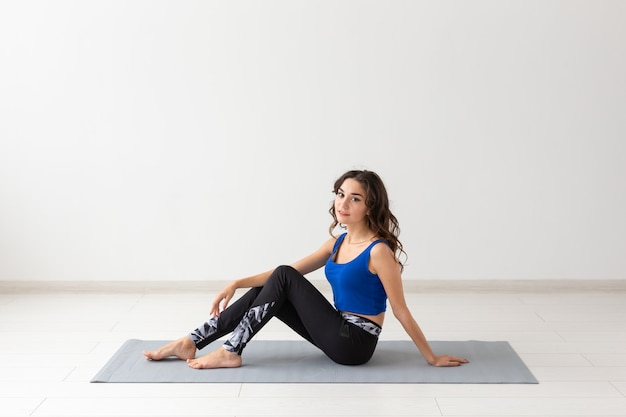 People, sport, yoga and healthcare concept. smiling young woman sitting on exercise mat.