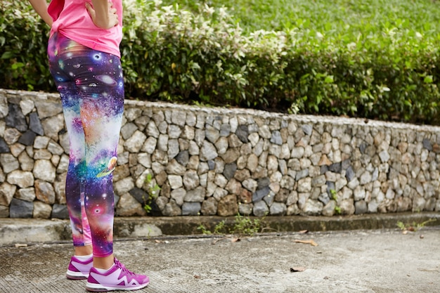People, sports and determination. cropped portrait of female runner wearing space print leggings and stylish running shoes, standing on pavement, keeping hands on her waist, getting ready for run