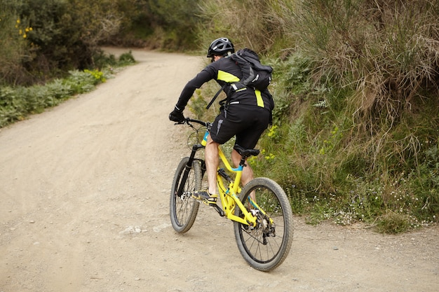 Concetto di stile di vita sano persone, sport, estremo, rischio e attivo. giovane ciclista maschio europeo che indossa abbigliamento da ciclismo e indumenti protettivi in sella a mountain bike giallo veloce lungo il sentiero nella foresta