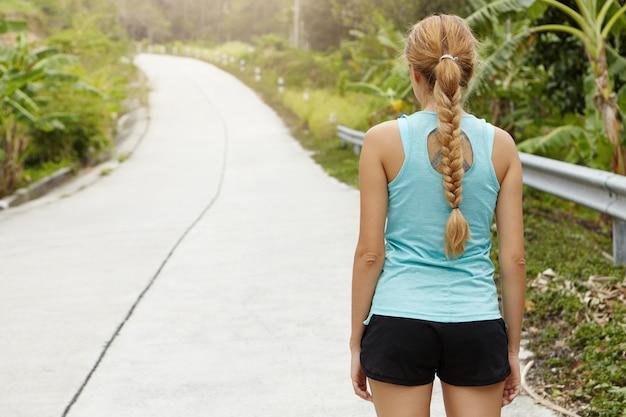 Persone, sport, fitness, resistenza e determinazione. vista posteriore della bionda sportiva caucasica con una lunga treccia in piedi sulla strada circondata da alberi tropicali, pronta per l'esecuzione.