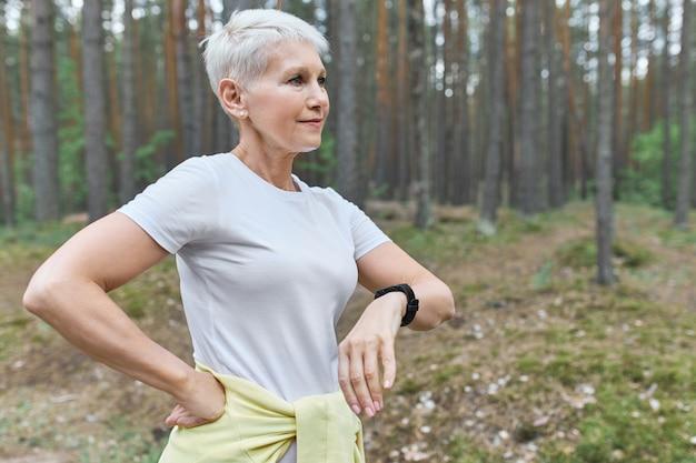 人、スポーツ、健康、テクノロジー。屋外での有酸素運動中の進行状況を追跡するためにスマートウォッチを身に着けているアクティブな引退した女性。