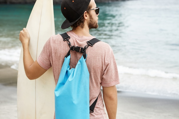 People, sports and hobby. young caucasian man wearing snapback and stylish sunglasses standing on sea shore with surfboard in his hands on sunny day