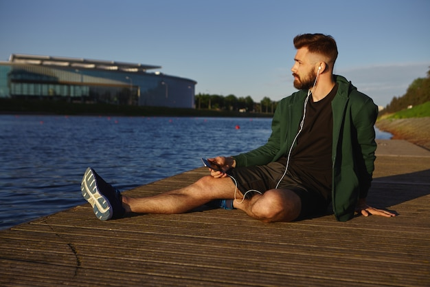 People, sports, modern lifestyle and technology concept. portrait of fashionable young bearded man wearing stylish clothes relaxing by lake in cityscape, listening to audiobook or music tracks