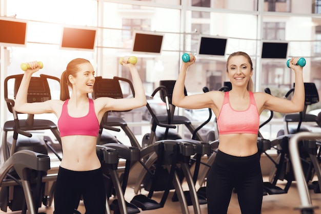 People in sportswear doing exercises with dumbbells at gym.