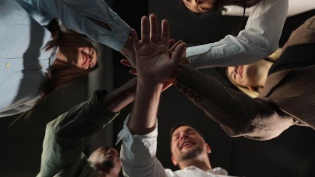 チームワークに接続された企業のチームビルディングに従事するパイルセールスチームで手を積み重ねる人々は、コーチングトレーニングの団結の概念をサポートするのに役立ちます底面図を閉じる