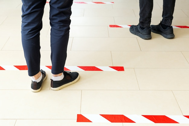 People stand in line keeping social distance, standing behind a warning line during covid 19 coronavirus quarantine