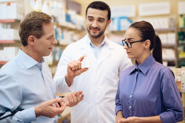 People stand in pharmacy and talk about something.