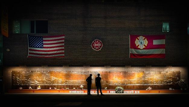 ニューヨークマンハッタンの記念碑の前に立っている人々
