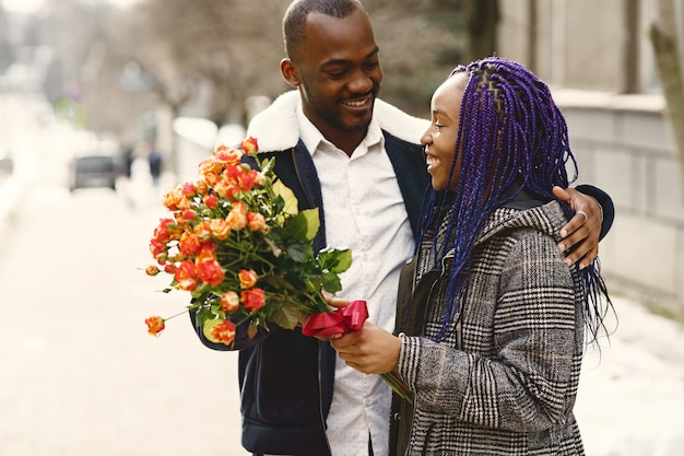 People standing outside. man gives flowers for female. african couple. valentine's day.
