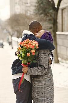 外に立っている人。男性は女性に花をあげます。アフリカのカップル。バレンタイン・デー。