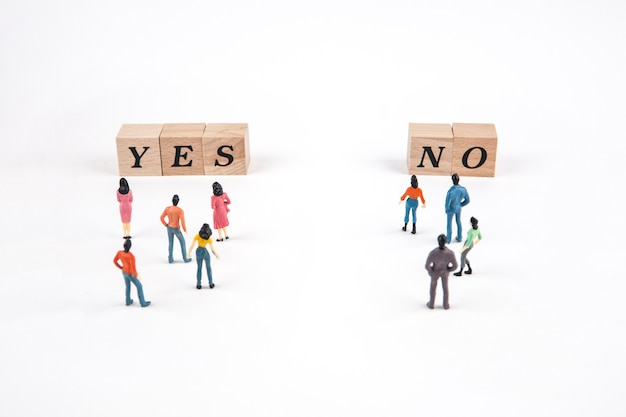 People standing at yes or no lettering cube on white