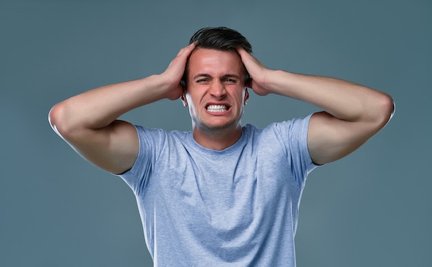 People, stress, tension and migraine concept. upset unhappy young man squeezing head with hands, suffering from headache