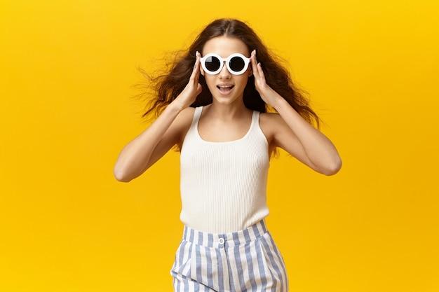 Persone, stile, bellezza e concetto di moda. colpo isolato di giovane donna alla moda allegra