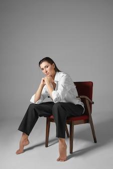 人、スタイル、ファッション、服、インテリアのコンセプト。男性のフォーマルな服を着て、足を大きく広げて男のように椅子に座っているスタイリッシュな美しい裸足の若い女性の縦の肖像画