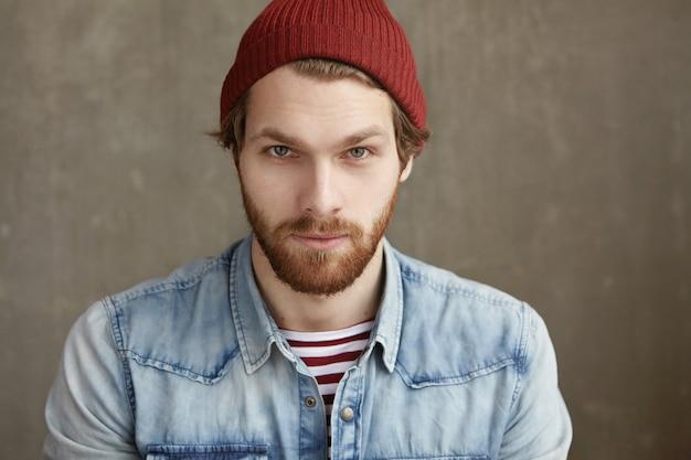 Concetto di persone, stile e moda. giovane modello maschio europeo bello con la barba alla moda che porta il cappello marrone rossiccio d'avanguardia e la camicia del denim che posano all'interno, osservando con il sorriso di flirt bello