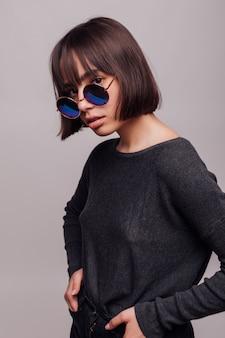 Concetto di persone, stile e moda - giovane donna felice o ragazza adolescente in abiti casual e occhiali da sole