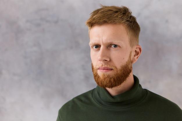 Persone, stile e concetto di moda. foto di attraente giovane uomo con la barba lunga alla moda con espressione facciale seria, non può nascondere il sospetto