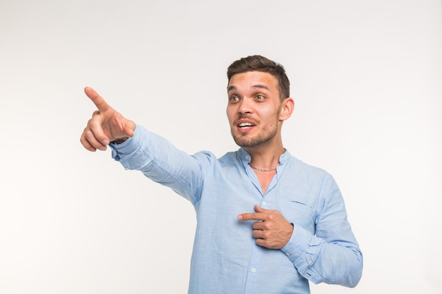 People, style and fashion concept - young handsome man in blue shirt over white background pointing.