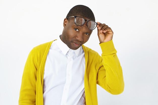사람, 스타일, 패션, 광학, 안경 및 비전 개념. 세련 된 젊은 어두운 피부 남자 스튜디오에서 포즈, 트렌디 한 눈 안경을 제기하고 회의적인 표정으로 카메라를 응시하는 사진