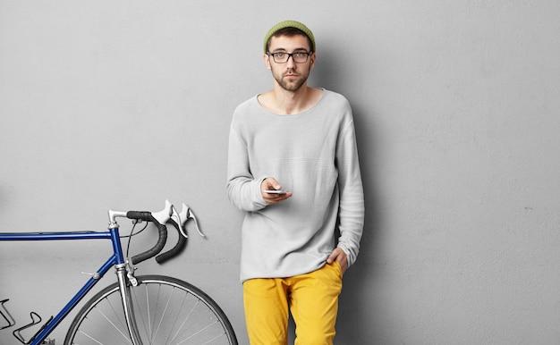 人、スタイル、ファッション、テクノロジー、コミュニケーションのコンセプト。携帯電話でメールをチェックする魅力的な若い白人男性フリーランサー