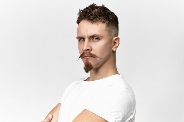 People, style, masculine beauty and fashion concept. close up image of handsome hipster guy with penetrative look, stylish mustache and goatee beard, posing in studio, being proud of himself