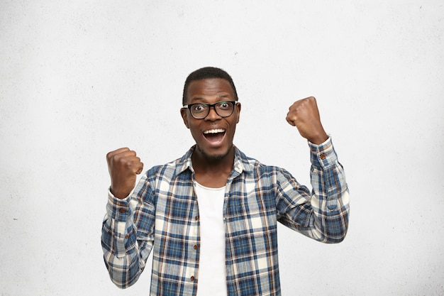 People, success, achievement and victory concept. successful young afro-american student screaming in excitement, clenching fists