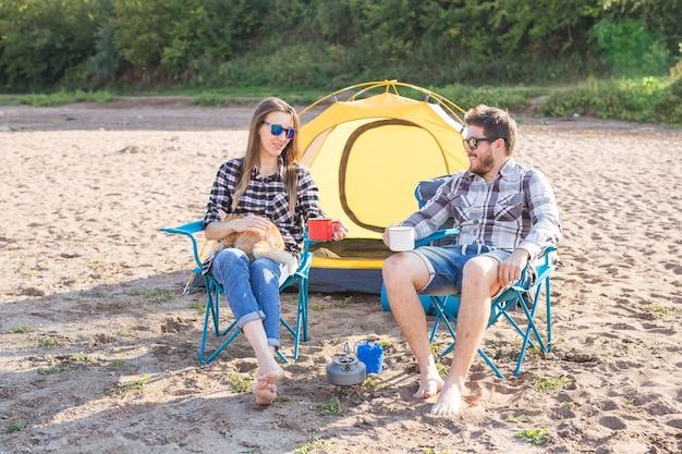 Люди, летний туризм и концепция природы - молодая пара пьет чай возле палатки