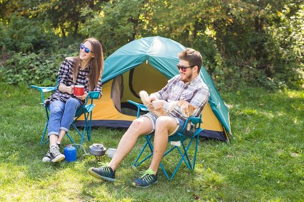 Люди, летний туризм и концепция природы - молодая пара сидит возле палатки