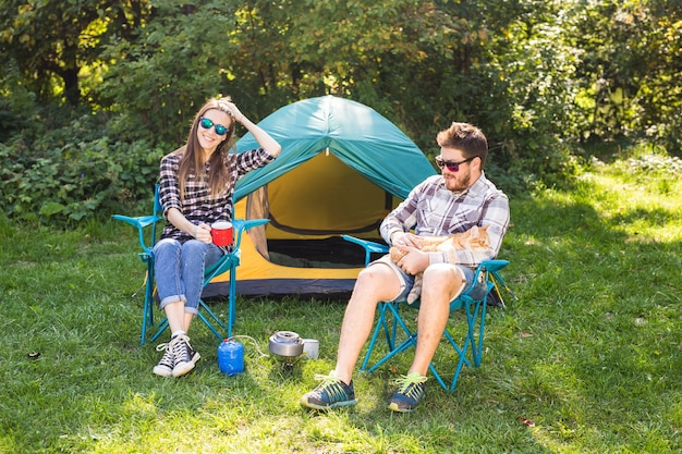 People, summer tourism and nature concept - young couple sitting near a tent.