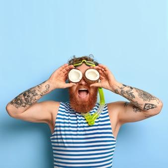 人々、夏休み、シュノーケリング、水泳のコンセプト。面白いひげを生やした生姜男はシュノーケルマスクを着用します