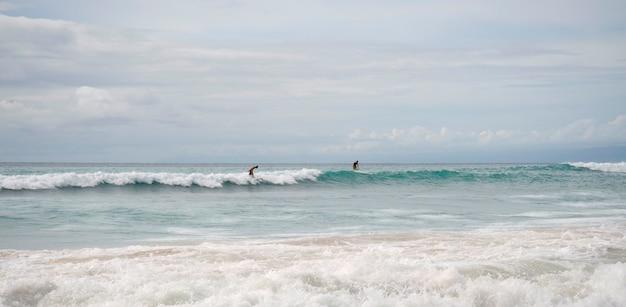 People surfing in ocean along coast of bali