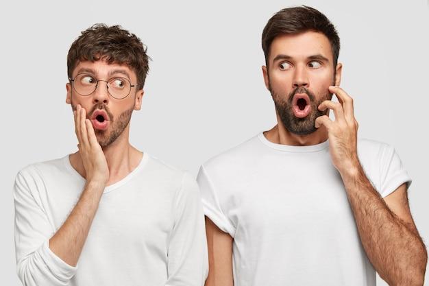 Persone e concetto di sorpresa. giovani uomini barbuti sbalorditi con la bocca ampiamente aperta e gli occhi infastiditi, si guardano l'un l'altro con espressioni scioccate, ascoltano notizie inaspettate, isolato su un muro bianco