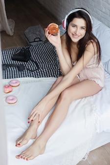 Люди, сладости и концепция быстрого питания - счастливая молодая женщина или девочка-подросток ест пончик, стоя на коленях в постели. красивая стройная сексуальная девушка лежит в постели со сладкими пончиками, время завтрака, концепция доброго утра