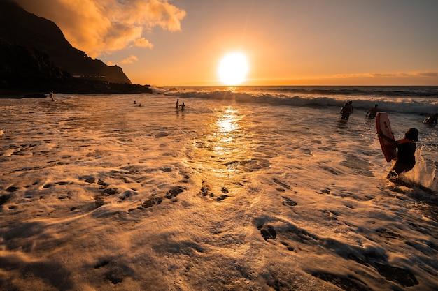 사람들은 저녁에 바다에서 수영하며 테 네리 페 섬의 아름다운 일몰을 감상합니다.