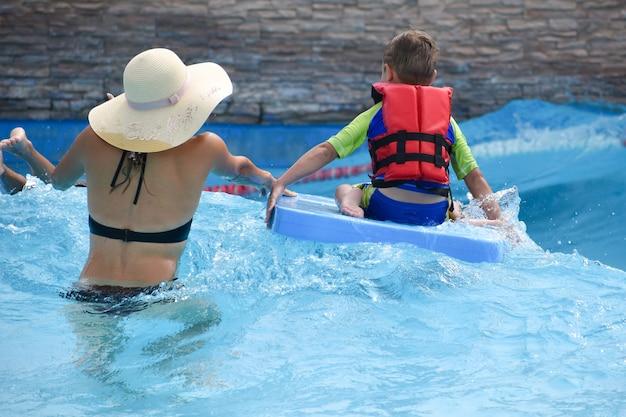 Летом люди плавают в аквапарке.