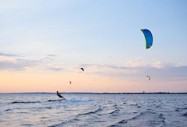 People swim in the sea on a kiteboard or kitesurfing