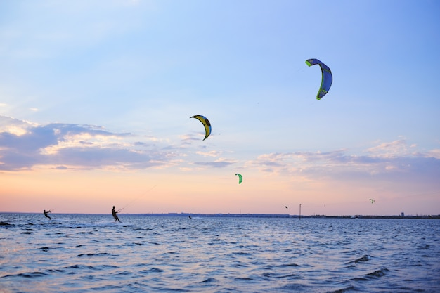 People swim in the sea on a kiteboard or kitesurfing
