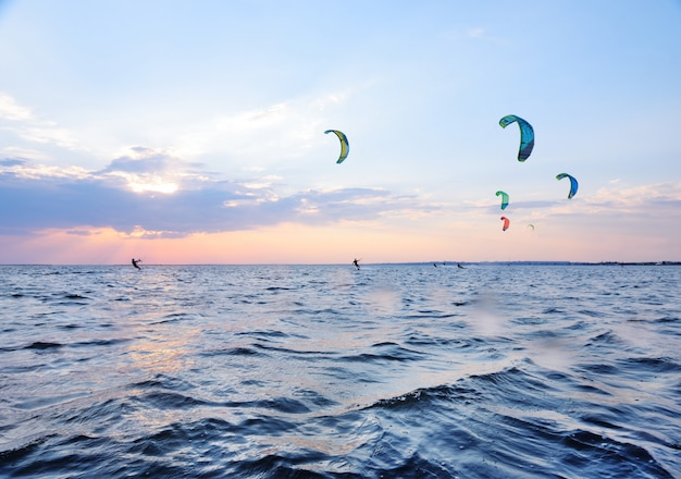 People swim in the sea on a kiteboard