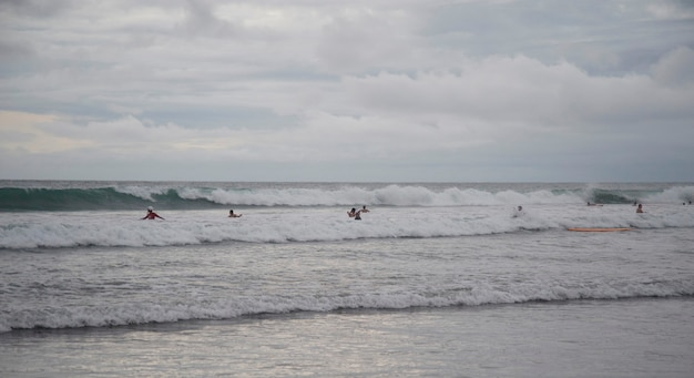 People swimming by shoreline in bali