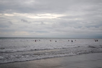 People swimming by the shoreline in Bali