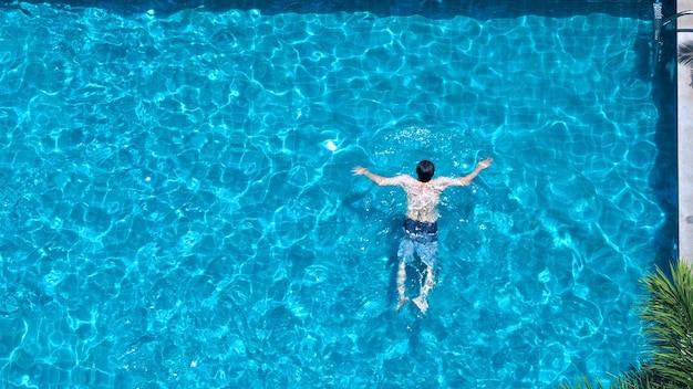 休暇の夏の日にホテルのプールで泳いだり、家族やトップビューで一緒に遊んだりする人々